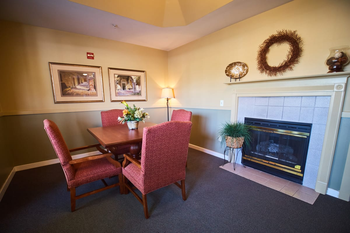 Room with a fireplace and a square table at Farmington Square Beaverton in Beaverton, Oregon