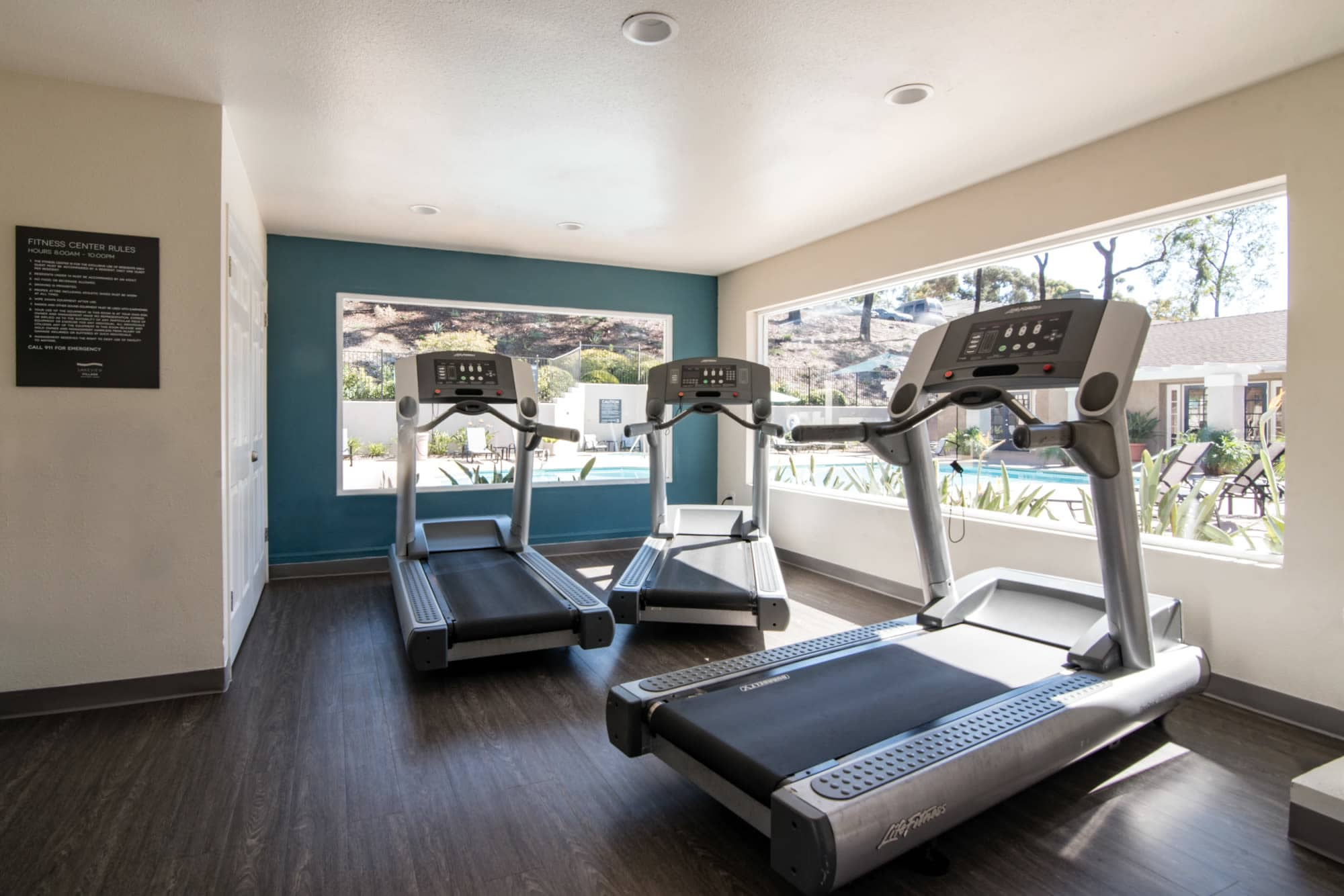 Newly renovated fitness center with large windows that look out to pool area at Lakeview Village Apartments in Spring Valley, California