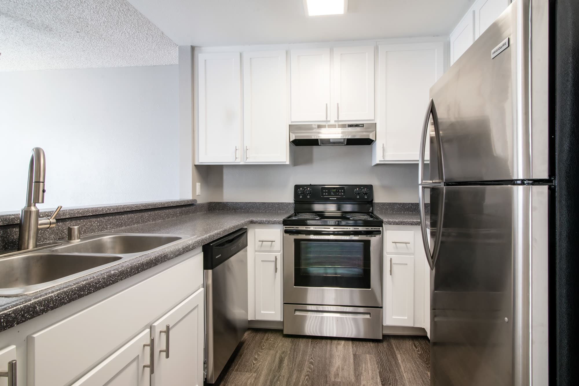 White renovated kitchen cabinetry with stainless steel appliances