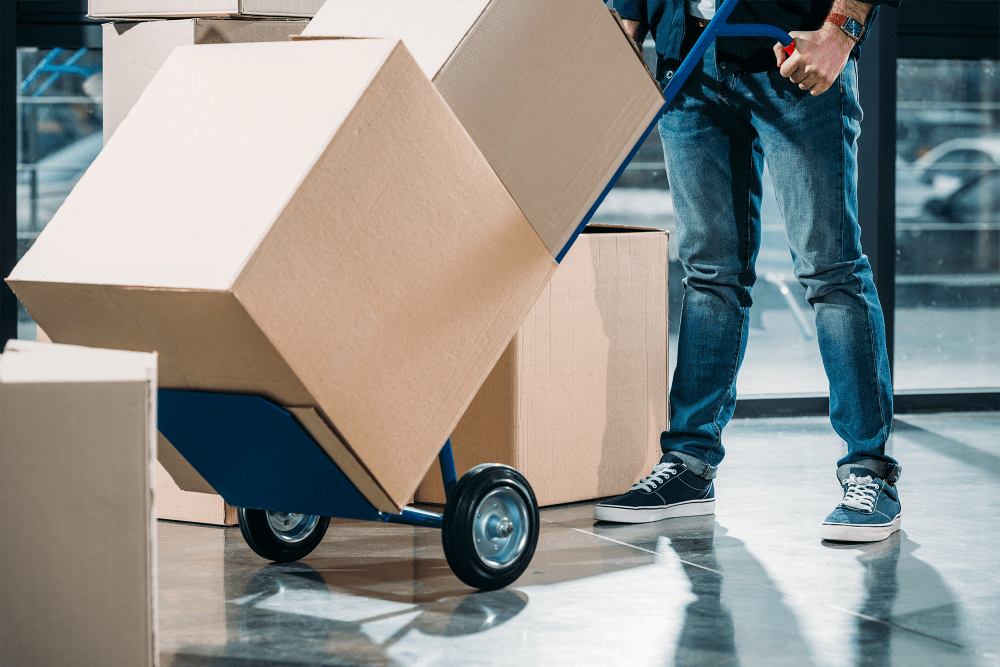 Man pushing dolly loaded with boxes at A-American Self Storage in Lancaster, California