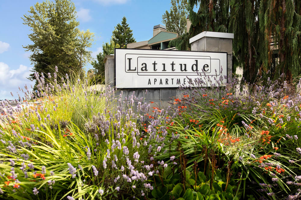 The monument sign surrounded by lush landscaping at Latitude Apartments in Everett, Washington