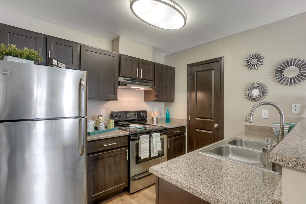 A kitchen complete with modern espresso cabinetry at Pebble Cove Apartments in Renton, Washington