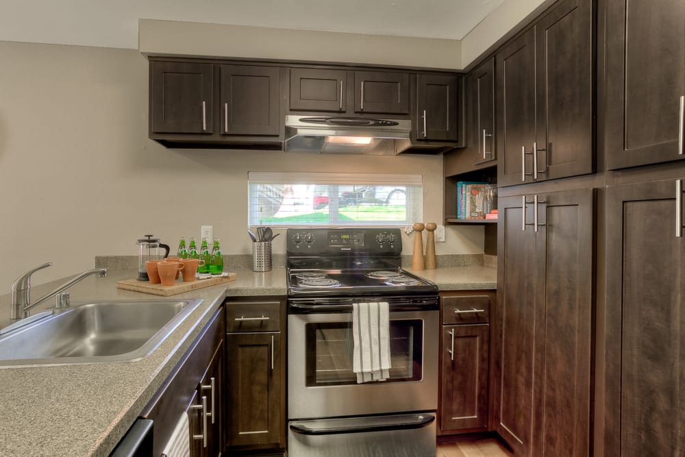 A kitchen complete with a brown cabinetry and stainless steel appliances at Park South Apartments in Seattle, Washington