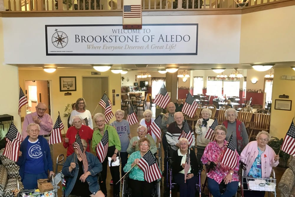 Residents celebrating with American flags at Brookstone of Aledo in Aledo, Illinois