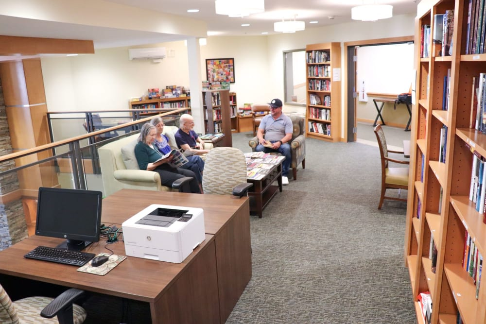 Residents sitting in library area at The Springs at Greer Gardens in Eugene, Oregon