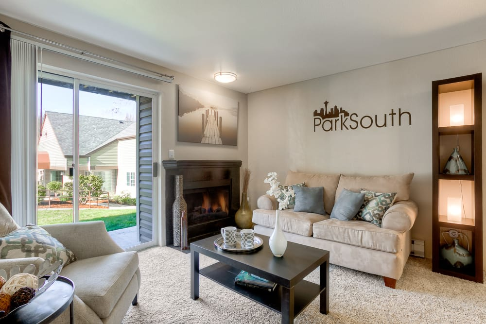 Sunny and spacious living room with a fireplace at Park South Apartments in Seattle, Washington