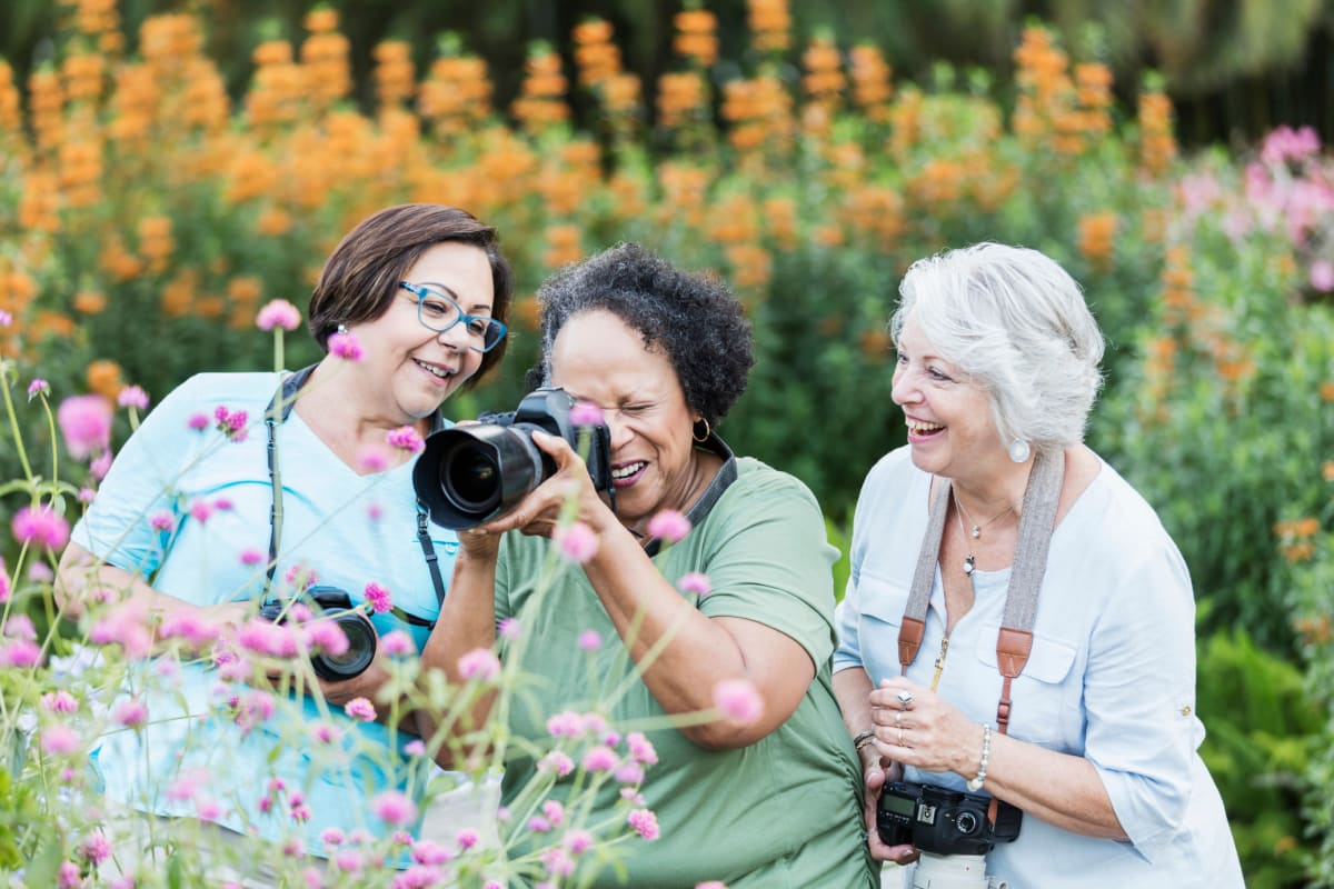 Ladies photographing flowers at Oxford Villa Active Senior Apartments in Wichita, Kansas