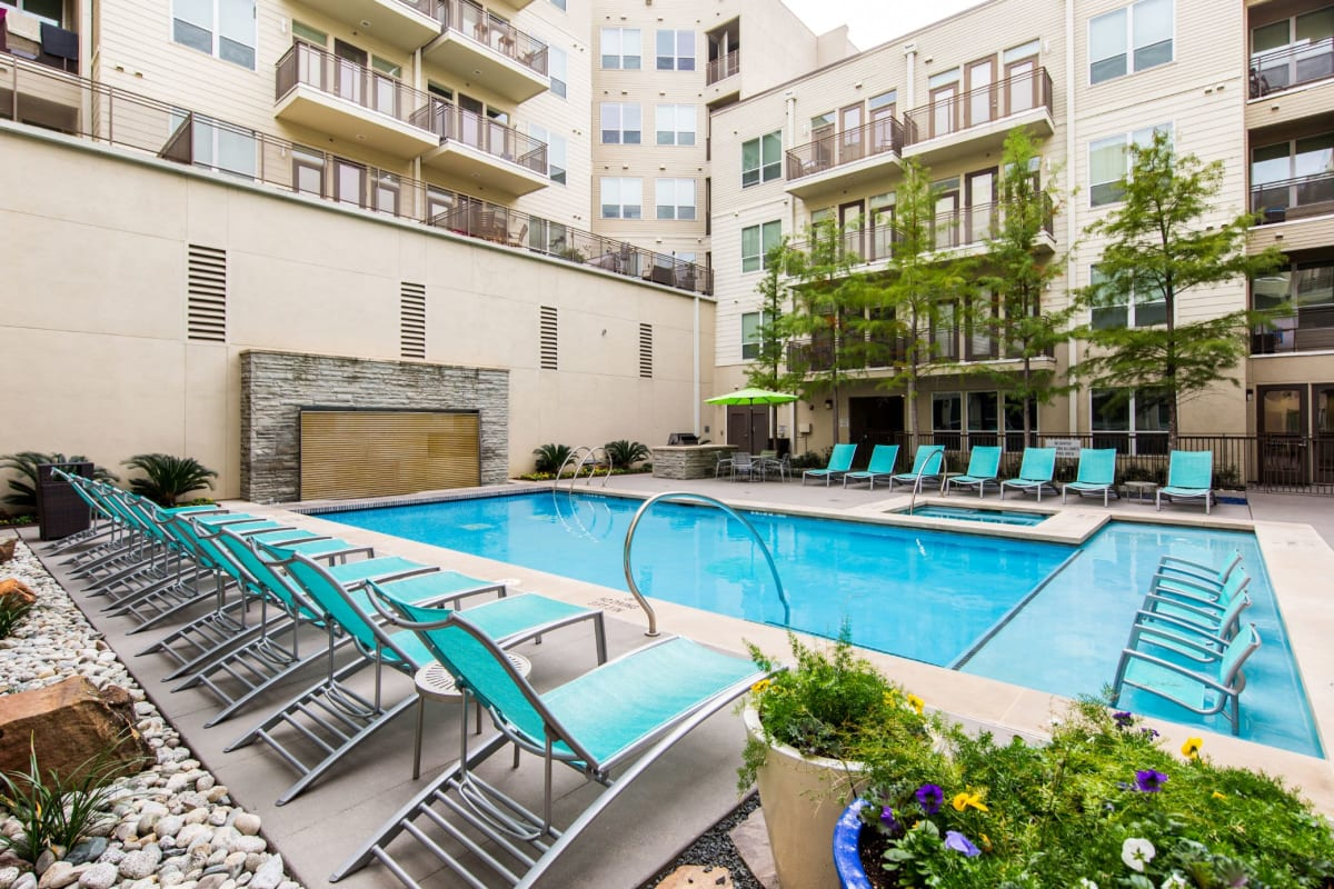Luxe swimming pool with lounge chairs on deck at The Marq on West 7th in Fort Worth, Texas
