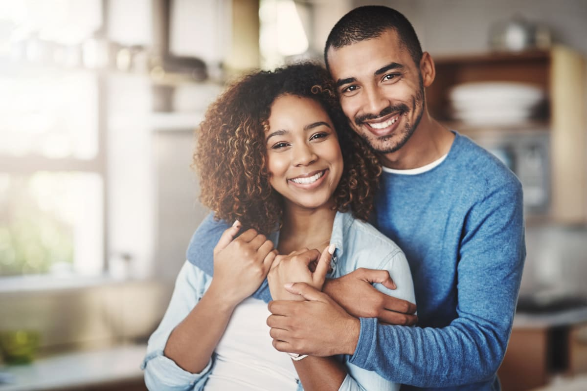 Couple smiling and embracing each other in their new apartment home at Fields on 15th Apartment Homes in Longmont, Colorado