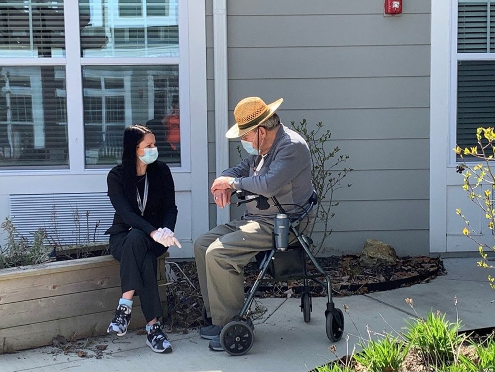 Resident sitting outside with a caretaker at a Anthology Senior Living location