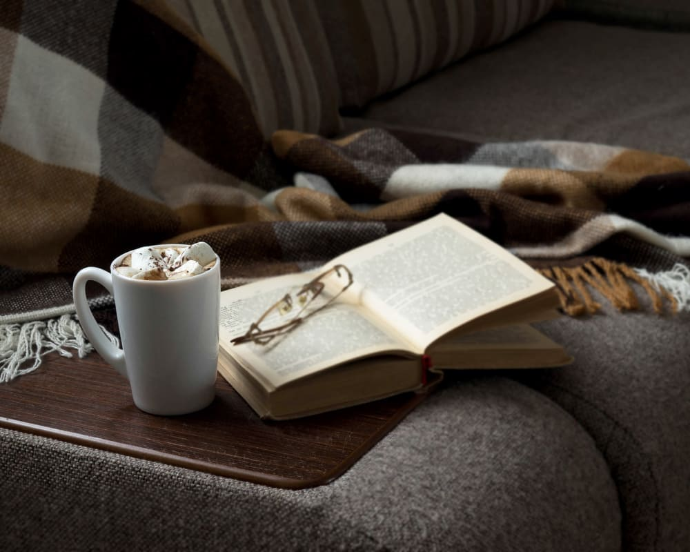 Cozy seating with a hot beverage and a book at The Arbors at Heritage Place in Lexington, Tennessee