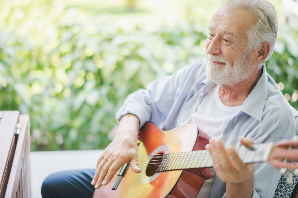 Resident playing the guitar at The Oxford Grand Assisted Living & Memory Care in Kansas City, Missouri