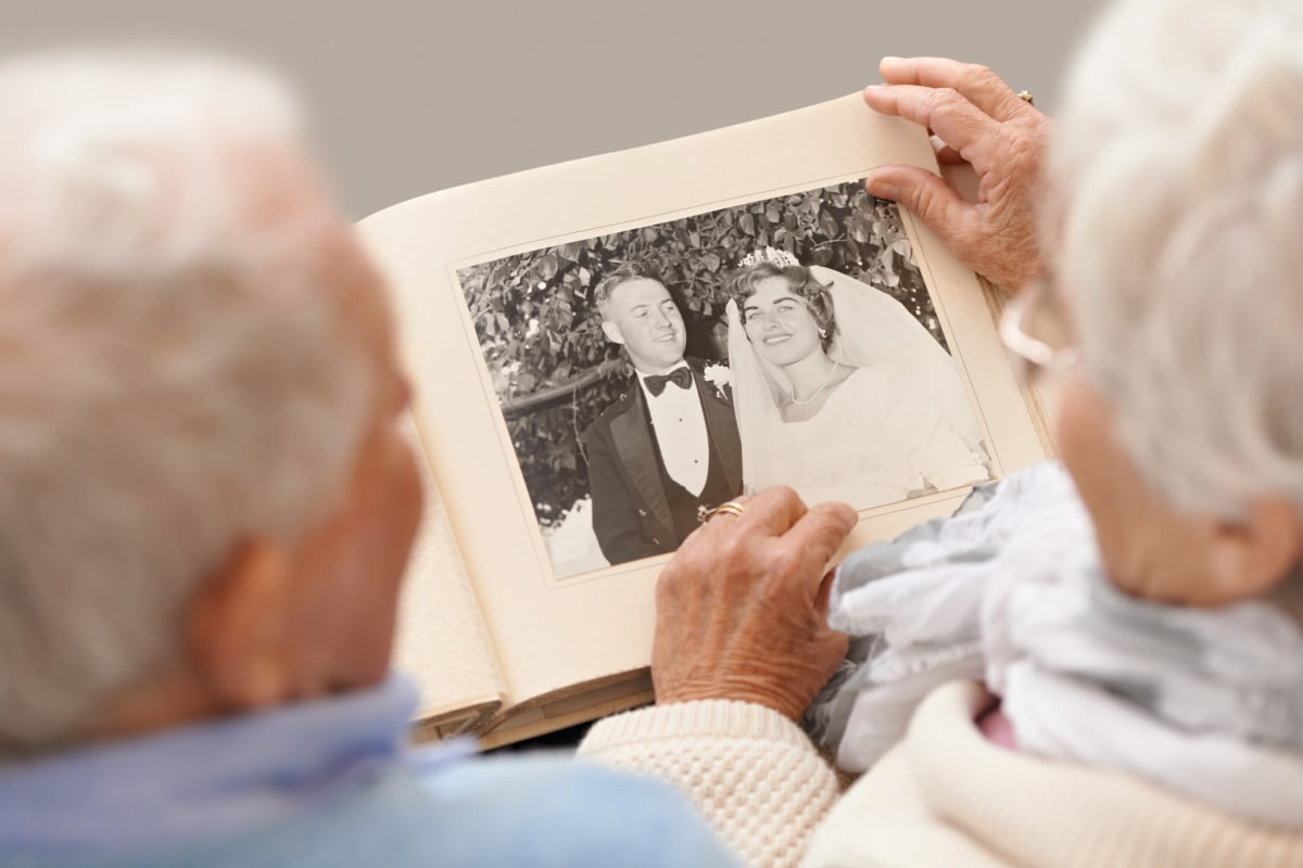 A couple of residents viewing a wedding album at Oxford Glen Memory Care at Carrollton in Carrollton, Texas
