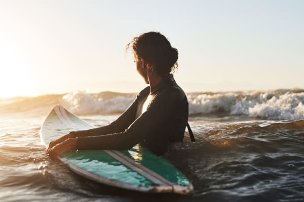 Woman in the ocean with a surfboard taken out of storage at a San Diego Self Storage location
