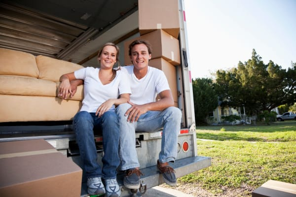 A couple loading up a moving truck, ready to move boxes to Global Self Storage in Edmond, Oklahoma