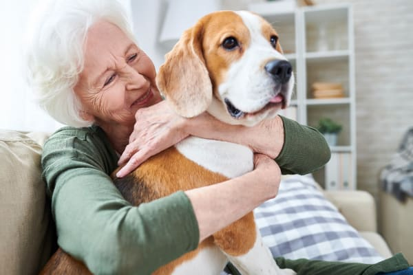 Happy resident hugging dog at Maplewood at Cuyahoga Falls in Cuyahoga Falls, Ohio