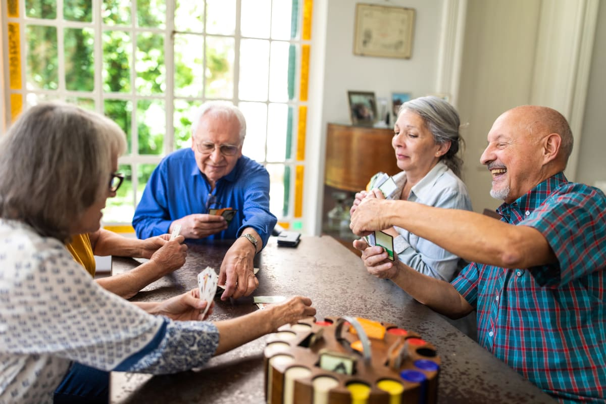 Residents laughing and playing a game at CERTUS Premier Memory Care Living in Orlando, Florida.