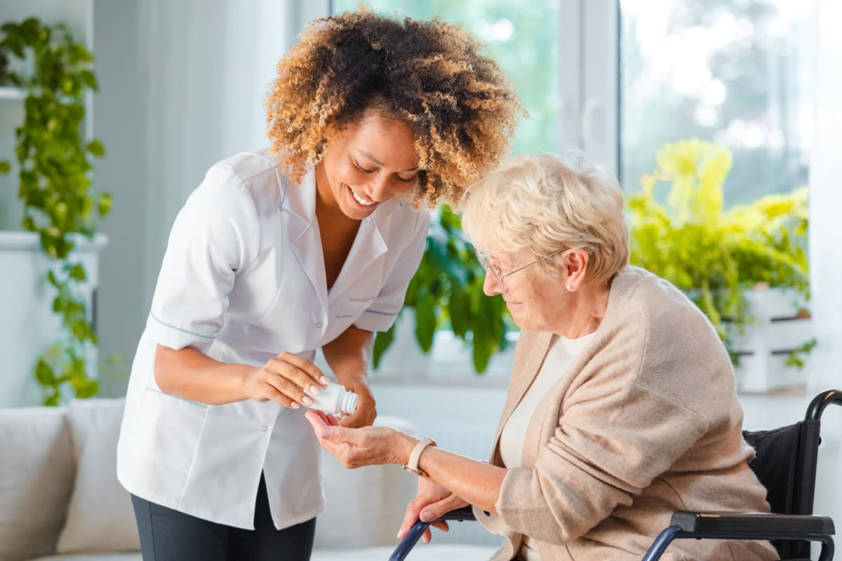 Resident receiving medication from a caretaker at South Pointe in Everett, Washington