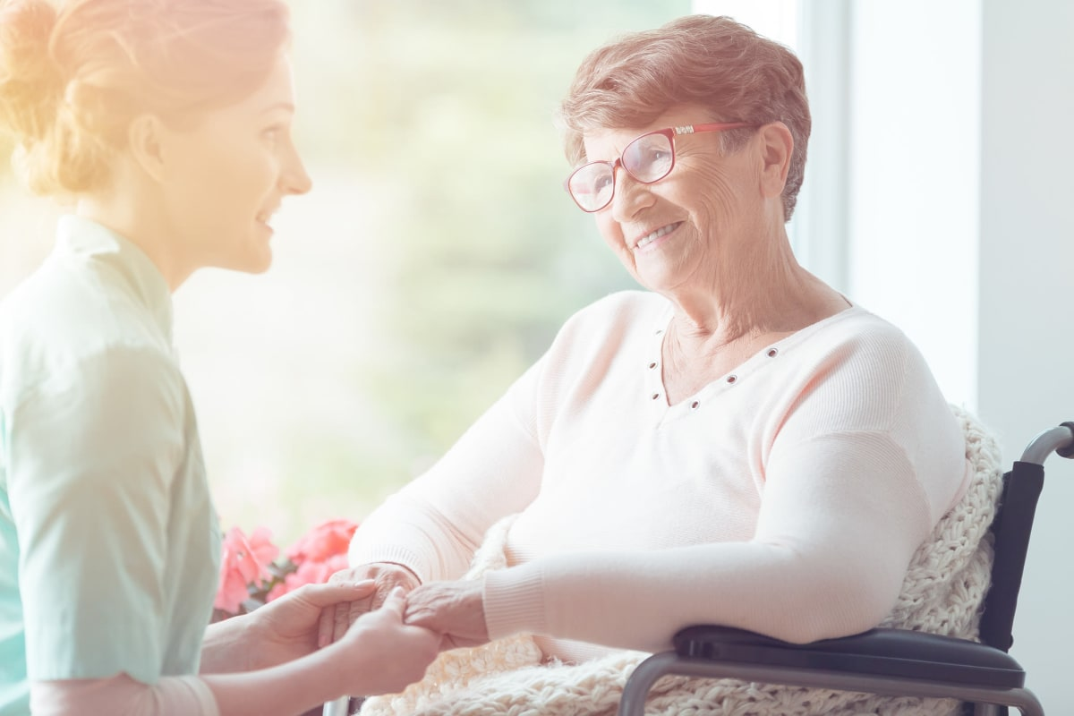 Resident holding hands and talking to a care specialist at The Mansions at Sandy Springs in Peachtree Corners, Georgia
