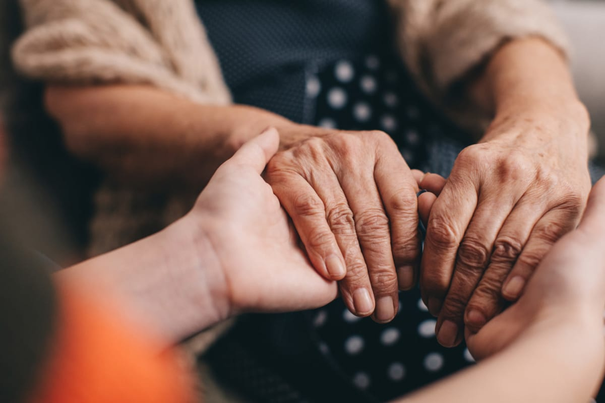A resident holding hands with a caregiver at Oxford Glen Memory Care at Sachse in Sachse, Texas
