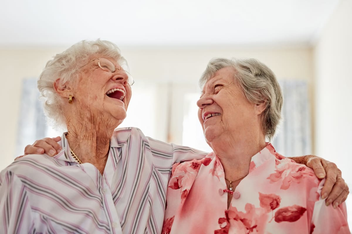 Two residents laughing together at The Oxford Grand Assisted Living & Memory Care in Wichita, Kansas