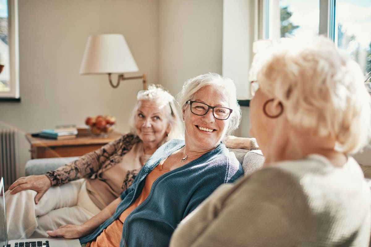 Three smiling friends sitting on a couch at Alderbrook Village in Arkansas City, Kansas