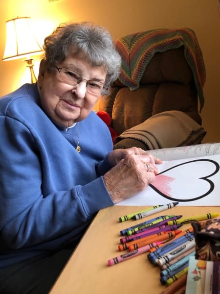 A resident coloring in a heart at Heritage Senior Living