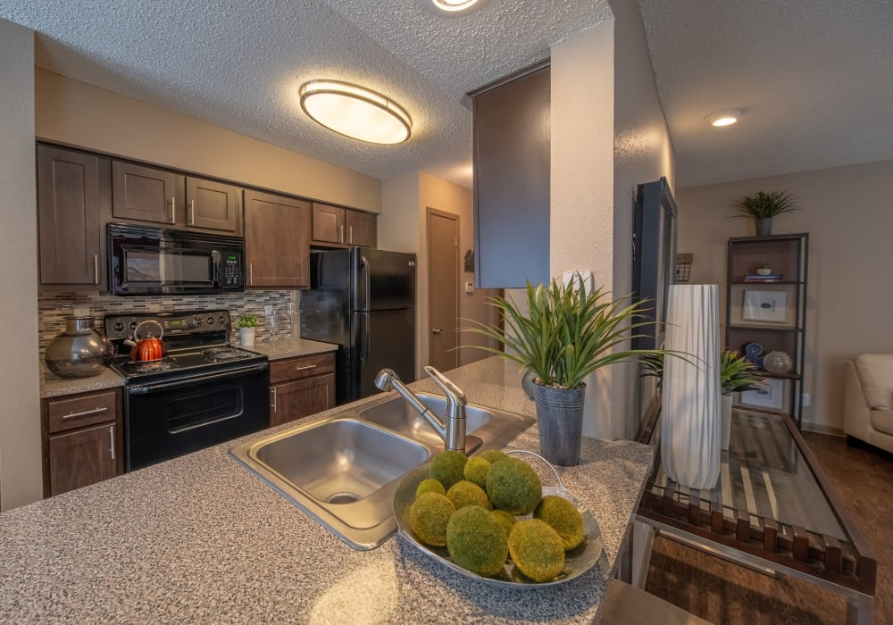 Model home's kitchen with a breakfast bar and custom wood cabinetry at Ridgeview Place in Irving, Texas