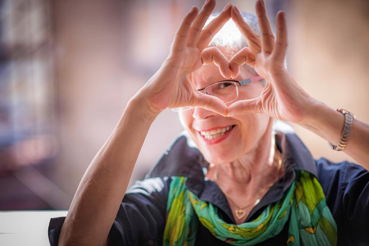 Woman making a heart shape at Milestone Retirement Communities