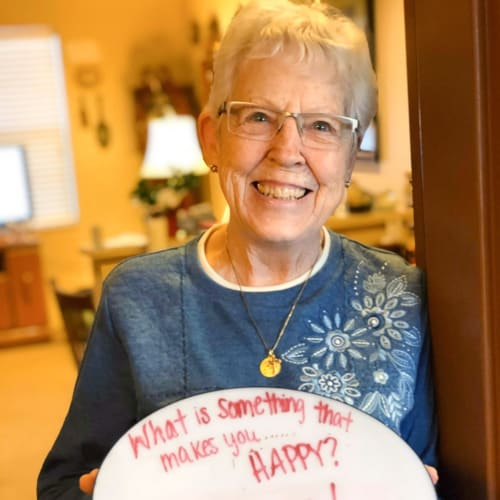 A happy resident standing in her doorway at The Oxford Grand Assisted Living & Memory Care in Wichita, Kansas