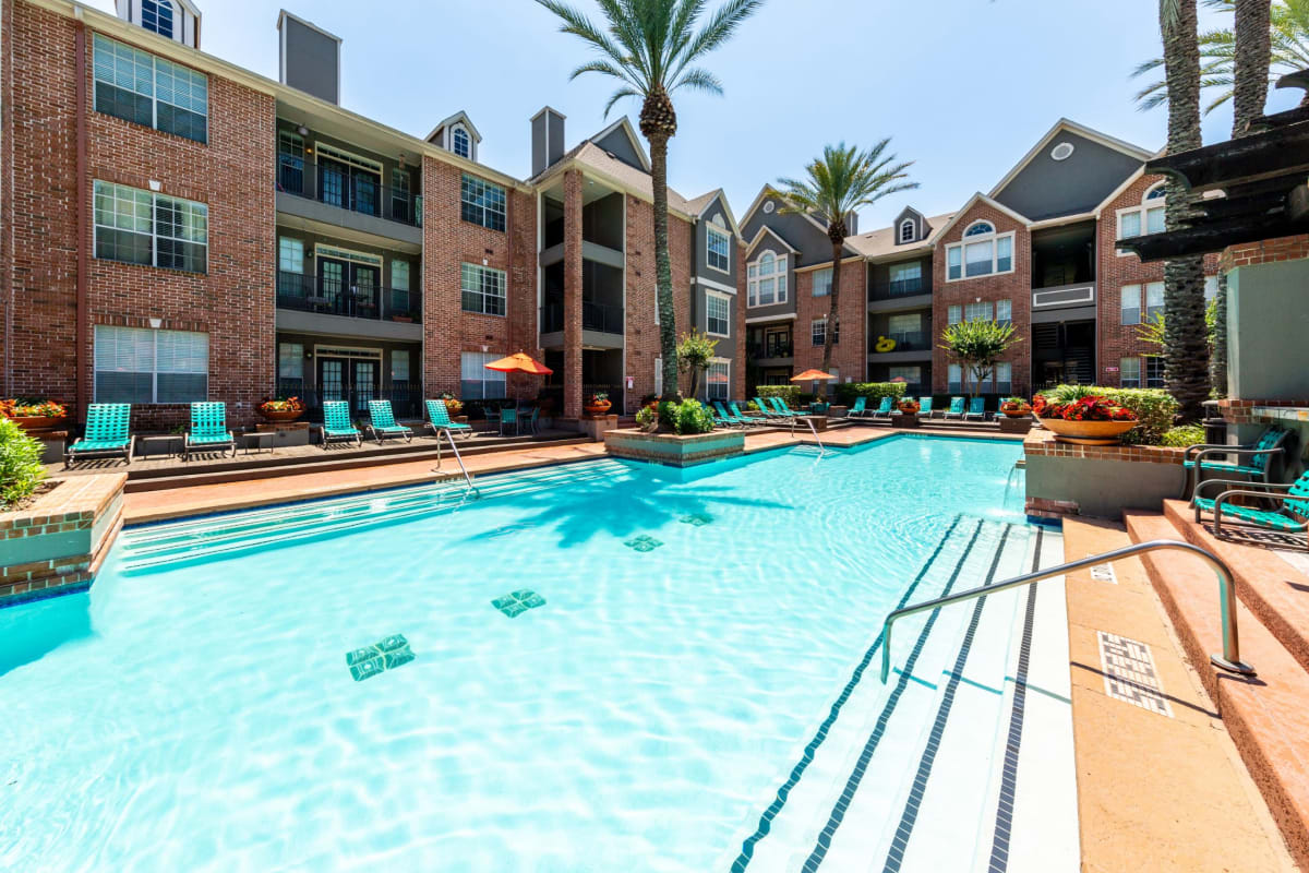 Resort style pool with lunge chairs on deck at Marquis on Pin Oak in Houston, Texas