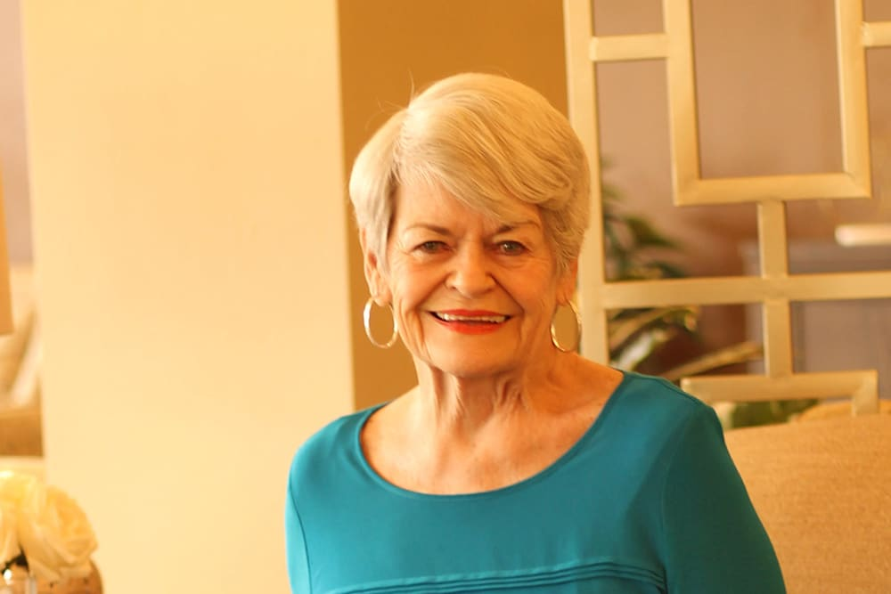 A resident smiling for the camera at Merrill Gardens at Rancho Cucamonga in Rancho Cucamonga, California.