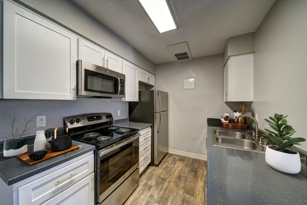 A kitchen with plenty of cabinet space at Parkside Commons Apartments in San Leandro, California