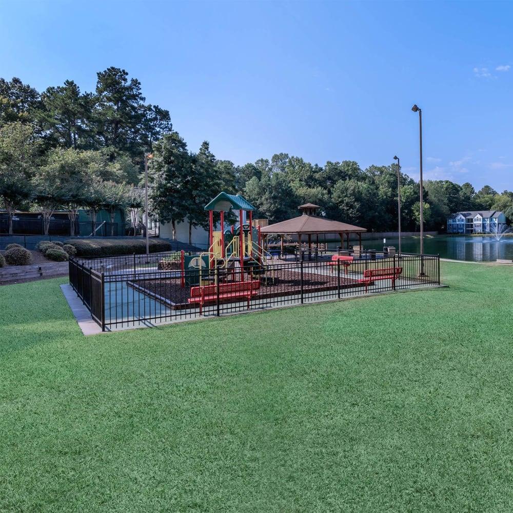 Fenced, onsite children's playground near the lake at The Bentley at Marietta in Marietta, Georgia
