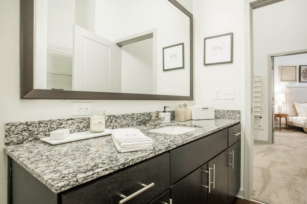 Master bathroom with large mirror, granite counter, and wood cabinets at Marq Midtown 205 in Charlotte, North Carolina