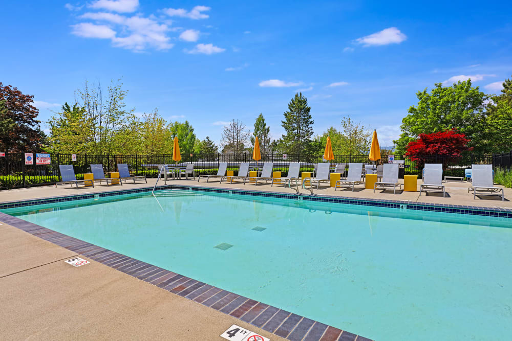 Beautiful resort-style swimming pool with lounge chairs at Cascade Ridge in Silverdale, Washington