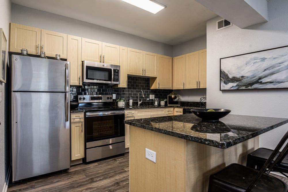 Stainless steel appliances and wood floors in kitchen at Ranch ThreeOFive in Arlington, Texas