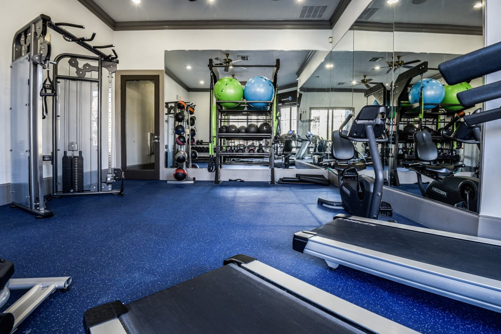 Fitness center with treadmills and large windows for natural lighting at Ranch ThreeOFive in Arlington, Texas