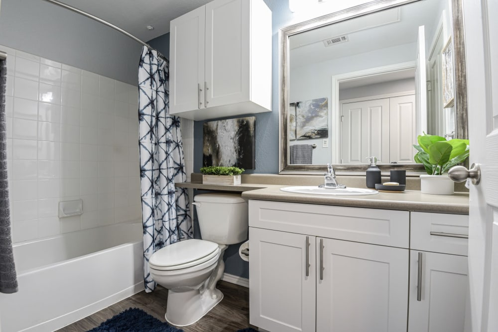 Bathroom with a large vanity mirror and oval tub at Ranch ThreeOFive in Arlington, Texas