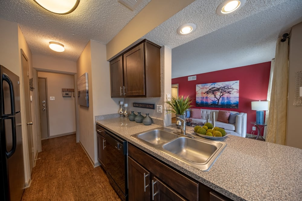 Granite countertops and a breakfast bar in a model home's kitchen at Ridgeview Place in Irving, Texas