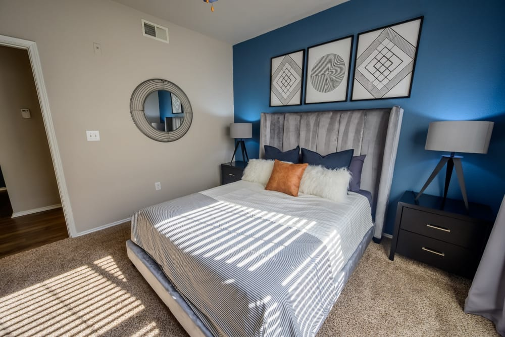 Plush carpeting and an accent wall in the primary bedroom of a model apartment at 23Hundred @ Ridgeview in Plano, Texas