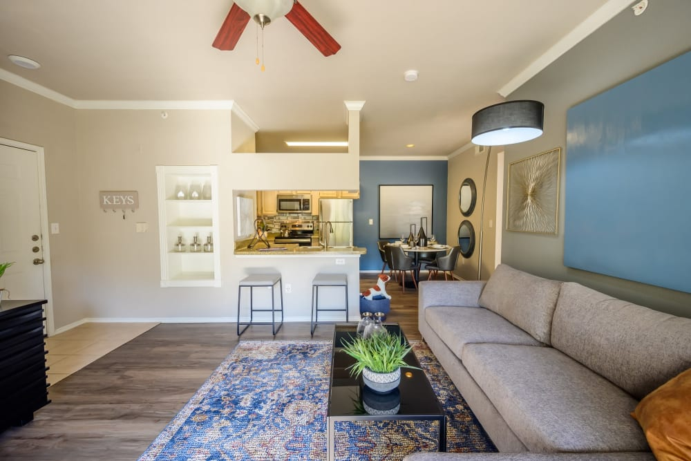 Open-concept model home's living area with a ceiling fan and hardwood flooring at 23Hundred @ Ridgeview in Plano, Texas