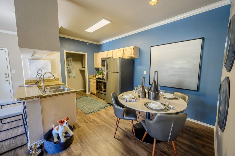 Dining area next to the kitchen with an accent wall in a model apartment at 23Hundred @ Ridgeview in Plano, Texas