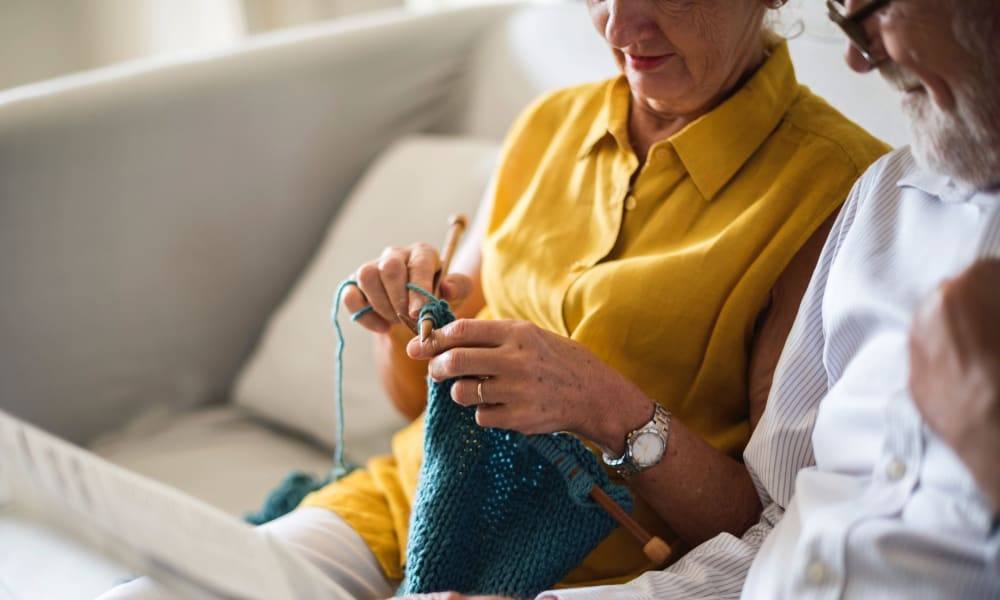 A resident knitting next to her husband on the couch at Randall Residence of Fremont in Fremont, Ohio