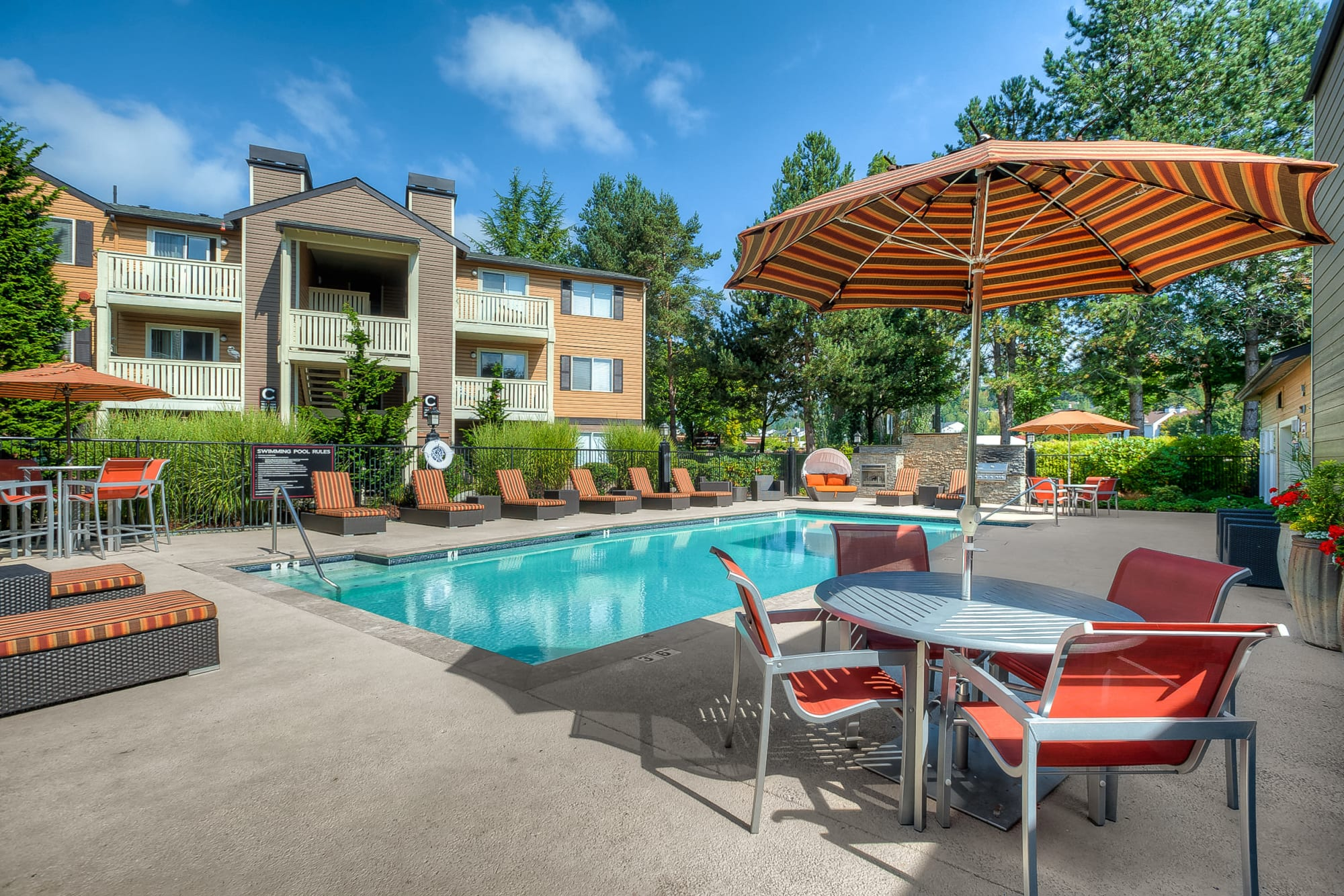 Sparking pool view with lounges, tables, umbrellas at Newport Crossing Apartments