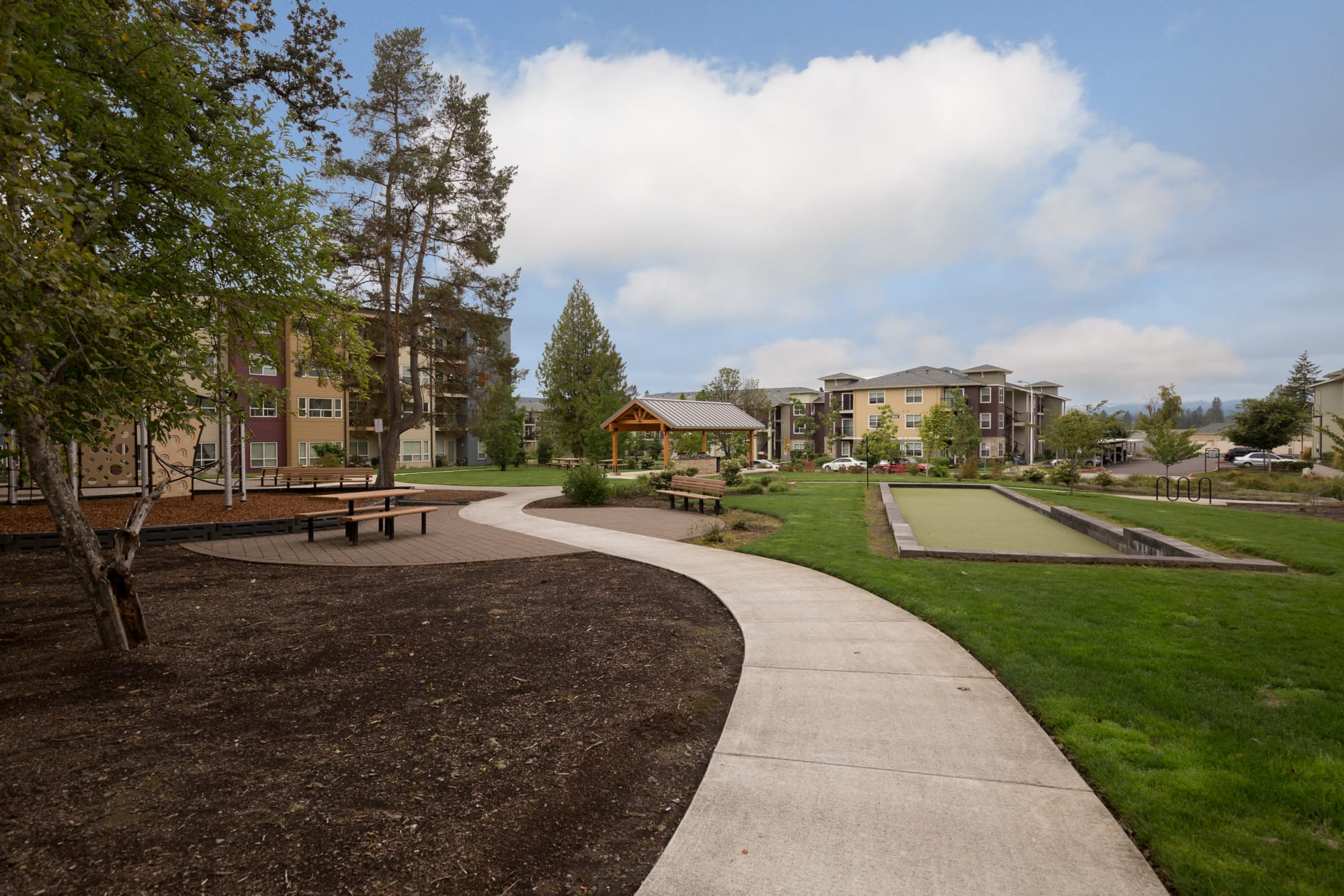 Outdoor Amenity Area with exercise locations, boce ball, open grass and playground at Terrene at the Grove