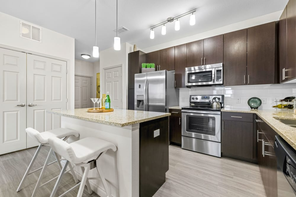 Kitchen featuring stainless steel appliances and breakfast bar seating at The Parc at Greenwood Village in Greenwood Village, Colorado