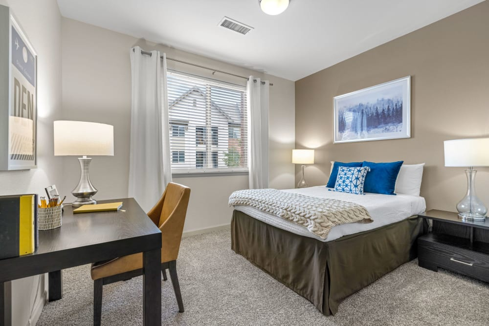 Spacious bedroom with abundant natural light from large window in an apartment at The Parc at Greenwood Village in Greenwood Village, Colorado