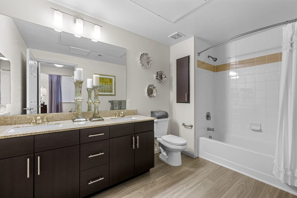 Spacious bathroom with large vanity mirror and bathtub shower at The Parc at Greenwood Village in Greenwood Village, Colorado