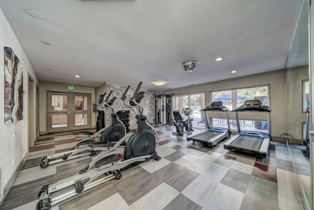 Fitness center with plenty of individual workout stations at The Timbers Apartments in Hayward, California